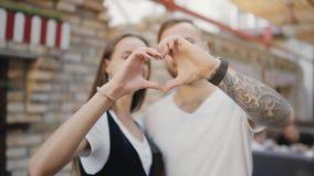Portrait d'un jeune couple europian attrayant riant et faisant une forme de coeur avec leurs mains dans le mouvement lent clips vidéos