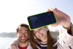 Portrait d'un jeune couple heureux prenant le selfie avec le téléphone portable Photo stock