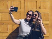 Portrait d'un jeune couple lesbien de sourire posant pour un selfie dans une porte jaune Bonheur et concept joyeux de mode de vie photographie stock libre de droits