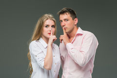 Portrait d'un jeune couple se tenant sur le fond gris Photo stock