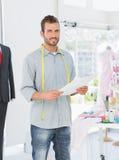 Portrait d'un jeune couturier masculin tenant le croquis Images libres de droits