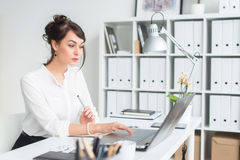 Portrait d'un jeune employé de bureau féminin s'asseyant sur son lieu de travail dans le bureau, dactylographie, regardant sur l' Image libre de droits