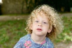 Portrait d'un jeune garçon avec les cheveux bouclés blonds image libre de droits
