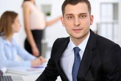Portrait d'un jeune homme d'affaires contre un groupe de gens d'affaires lors d'une réunion Photo libre de droits
