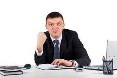 Portrait d'un jeune homme d'affaires fâché te montrant son poing d'isolement sur le fond blanc Photos stock