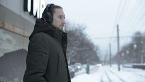 Portrait d'un jeune homme aux cheveux longs avec une barbe dans des écouteurs se tenant à un arrêt de tram en hiver et attendant  clips vidéos