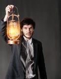 Portrait d'un jeune homme avec la lampe à pétrole images stock