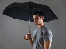 Portrait d'un jeune homme avec un parapluie noir Photos libres de droits