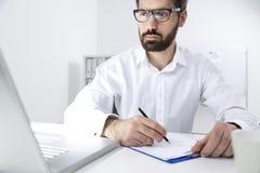 Portrait d'un jeune homme barbu prenant des notes photographie stock