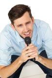 Portrait d'un jeune homme chantant dans le microphone Photographie stock