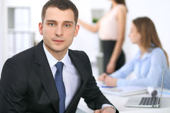 Portrait d'un jeune homme d'affaires contre un groupe de gens d'affaires lors d'une réunion Images libres de droits