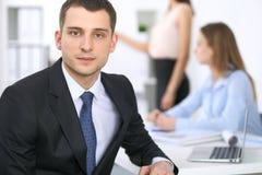 Portrait d'un jeune homme d'affaires contre un groupe de gens d'affaires lors d'une réunion Photos libres de droits