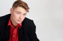 Portrait d'un jeune homme d'affaires utilisant un costume noir et une chemise rouge. Homme recherchant. Images libres de droits