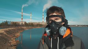 Portrait d'un jeune homme dans un masque de respirateur ou de gaz À l'arrière-plan la fumée vient des tuyaux d'un hydro-élect banque de vidéos