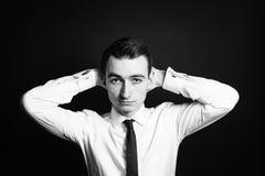 Portrait d'un jeune homme dans une chemise blanche, mains derrière la tête image libre de droits