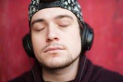 Portrait d'un jeune homme de détente beau dans une casquette de baseball et des écouteurs de port sur un fond rouge photos stock