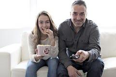 Portrait d'un jeune homme et d'une fille regardant la TV tout en mangeant du maïs éclaté sur le sofa photos stock