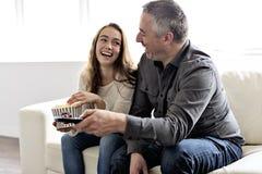 Portrait d'un jeune homme et d'une fille regardant la TV tout en mangeant du maïs éclaté sur le sofa images libres de droits