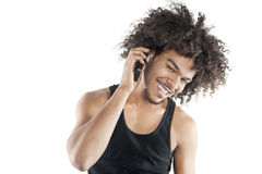 Portrait d'un jeune homme heureux écoutant le téléphone portable au-dessus du fond blanc Photographie stock
