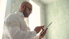 Portrait d'un jeune homme heureux beau à l'aide de la Tablette de Digital banque de vidéos
