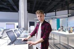 Portrait d'un jeune homme positif dans le magasin de l'électronique tout en choisissant un ordinateur portable photos libres de droits