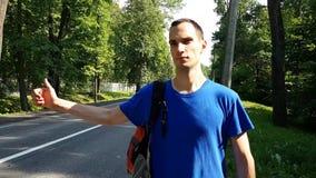 Portrait d'un jeune homme qui arrête une voiture de dépassement du côté de la route Les sourires avec du charme de jeune homme Ac banque de vidéos