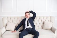 Portrait d'un jeune homme sérieux et sûr dans un costume se reposant sur le divan et regardant l'appareil-photo photographie stock libre de droits