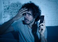 Portrait d'un jeune homme semblant TV de observation effray?e et choqu?e Expressions et ?motions humaines photo stock