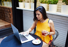 Portrait d'un jeune indépendant féminin à l'aide de l'ordinateur portable pour le travail de distance tout en se reposant dans l' Images libres de droits