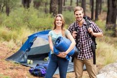 Portrait d'un jeune joli couple de randonneur tenant un sac de couchage et un sac à dos photo stock