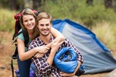 Portrait d'un jeune joli couple de randonneur tenant un sac de couchage et un sac à dos Image stock
