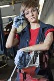 Portrait d'un jeune mécanicien féminin utilisant l'eyewear protecteur dans le garage images stock