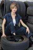 Portrait d'un jeune mécanicien s'asseyant sur des pneus dans l'atelier de voiture photos libres de droits