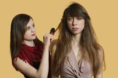 Portrait d'un jeune modèle femelle obtenant lui des cheveux dénommés au-dessus du fond coloré image libre de droits