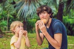 Portrait d'un jeune père et de son fils appréciant un hamburger en parc et sourire photo stock