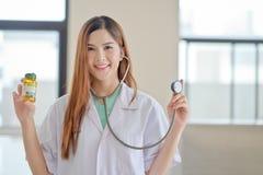 Portrait d'un jeune pharmacien montrant des pilules Photographie stock libre de droits