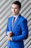 Portrait d'un jeune type dans un costume bleu sur un fond blanc images stock