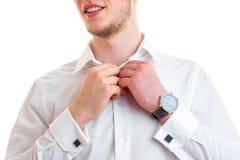 Portrait d'un jeune type qui sourit et le plan rapproché de chemise de mains de bouton Images stock