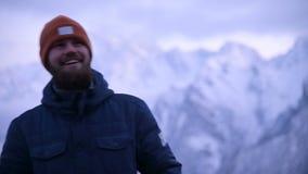 Portrait d'un jeune voyageur masculin barbu au crépuscule dans les montagnes Position pensante et souriante pour raisonner banque de vidéos