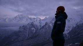 Portrait d'un jeune voyageur masculin barbu au crépuscule dans les montagnes Support sérieusement pensant et regardant autour cha banque de vidéos