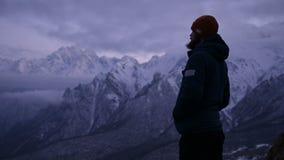 Portrait d'un jeune voyageur masculin barbu au crépuscule dans les montagnes Support sérieusement pensant et regardant autour cha clips vidéos
