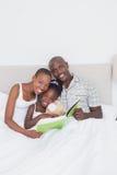 Portrait d'un joli couple lisant un livre avec leur fille dans le lit Photo stock