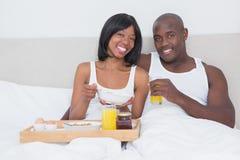 Portrait d'un joli couple prenant le petit déjeuner dans le lit ensemble Photo libre de droits