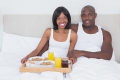Portrait d'un joli couple prenant le petit déjeuner dans le lit ensemble photographie stock