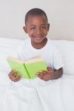 Portrait d'un livre de lecture de petit garçon dans le lit photo libre de droits