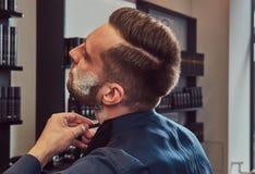 Portrait d'un mâle élégant qui lui-même rasant dans un salon de coiffure photos stock