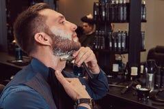 Portrait d'un mâle élégant qui lui-même rasant dans un salon de coiffure images libres de droits