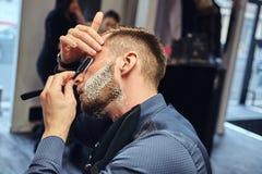 Portrait d'un mâle élégant qui lui-même rasant dans un salon de coiffure images stock