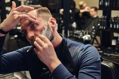 Portrait d'un mâle élégant qui lui-même rasant dans un salon de coiffure image libre de droits