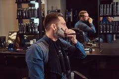 Portrait d'un mâle élégant qui lui-même rasant dans un salon de coiffure photographie stock
